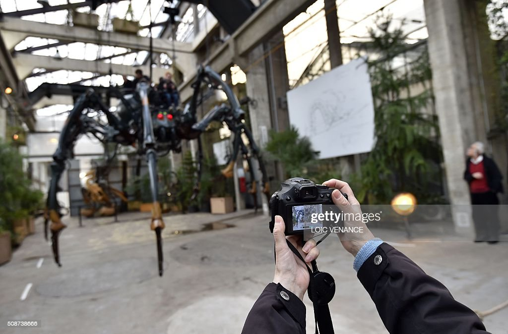 A man takes a picture of a mechanical spider made of wood and steel as it is presented to the public for the first time at 'Les Machines de L'Ile' ('Machines of the Isle of Nantes') in Nantes, western France, on February 6, 2016. / AFP / LOIC VENANCE