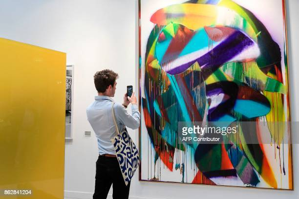 A man takes a picture of a painting by German artist Katharina Grrosse as he visits the Paris International Contemporary Art Fair at the Grand Palais...