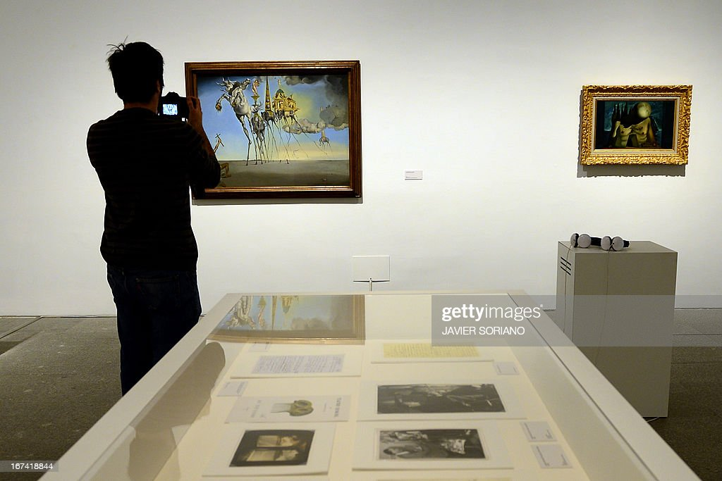 A man takes a picture of a painting entitled 'The Temptation of St.Anthony' (1946) by Spanish surrealist artist Salvador Dali during the exhibition 'Dali. All of the poetic suggestions and all of the plastic possibilities' at the Reina Sofia museum in Madrid on April 25, 2013.
