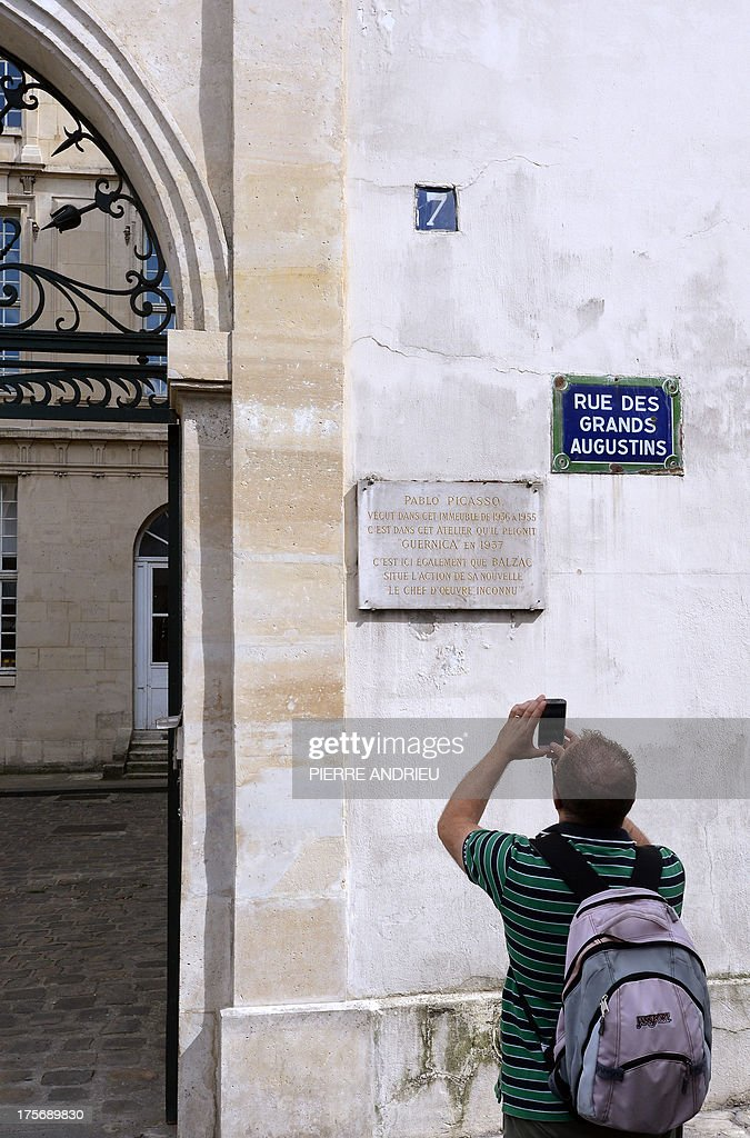 A man takes a picture of a plaque, on August 6, 2013 in Paris, which informs that Spanish artist Pablo Picasso lived in this buiding, in a place called 'Grenier Picasso' (Picasso Attic) from 1936 to 1955. Threatened with imminent eviction, the association, dedicated to artistic education, that runs the Attic Picasso, asked the government today not to provide assistance to police force as a new lawsuit is pending. Picasso created one of his major works 'Guernica' in this studio in 1937.