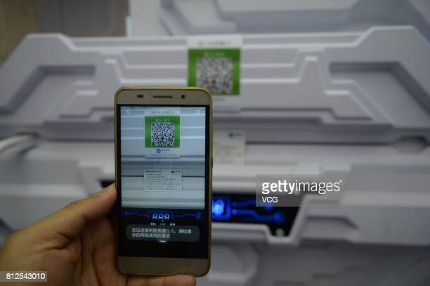 A man takes a picture of a QR code of the 'sleepsharing' capsules at a hotel in Zhongguancun on July 11 2017 in Beijing China Customers can rent the...