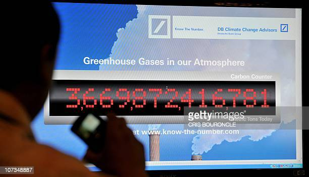 A man takes a picture of a screen showing a counter constantly updating the greenhouse gases in the Earth�s atmosphere during sideline activities of...