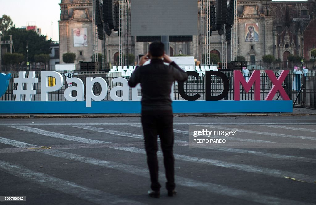 A man takes a picture of a sign referring to the visit of Pope Francis to Mexico City, in the Mexican capital on February 12, 2016 hours before the arrival of the pontiff to the country. Pope Francis left Rome on Friday bound for Cuba, where he is to hold a historic meeting Russian Patriarch Kirill before continuing on to Mexico for a five-day visit. AFP PHOTO / Pedro PARDO / AFP / Pedro PARDO