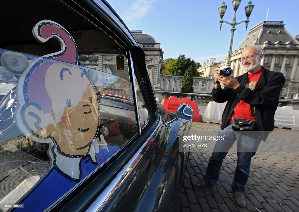 A man takes a picture of a vehicle of 'Tintin magazine' car rally on September 8, 2013 in Brussels. This unusual rally features real cars and motorbikes inspired by vehicles illustrated in the pages of Tintin's Diary at the occasion of Brussels' comic book festival. AFP PHOTO/JOHN THYS