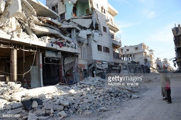 Graphic content / A man takes a picture of destroyed buildings on a street in the northwestern border town of alBab on February 23 2017 after...