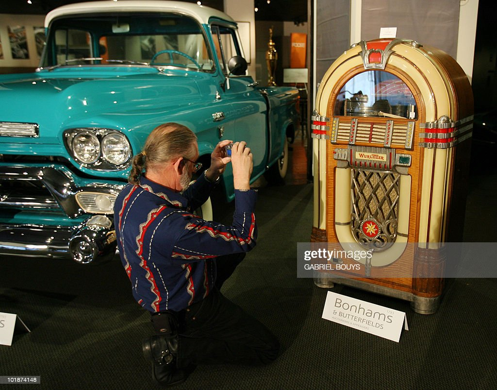 A man takes a picture of late US movie star Steve McQueen's Wurlitzer jukebox 06 November 2006 in Los Angeles. An auction of McQueen collectors' items will be organized 11 November at the Petersen Automotive museum. The sale will feature motorcycles, motorcycle clothing, knives, saddles and other memorabilia. AFP PHOTO/Gabriel BOUYS