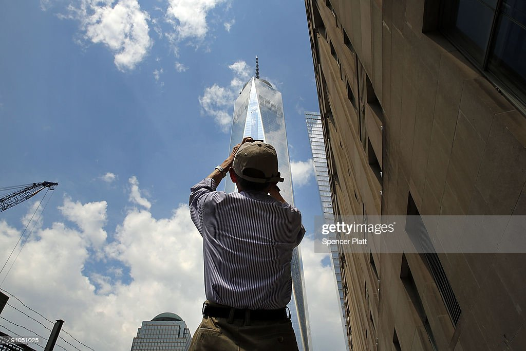 A man takes a picture of One World Trade Center on May 27, 2014 in New York City. With months before it's sceduled to open, the owners of One World Trade are cutting office rents due to a scarcity of current renters at the iconic location built near the former location of the original World Trade Center buildings, which were destroyed in the September 11 terrorist attacks. With only 55% of current space leased, owners and developers of the building are cutting rents 10% to $69 a square foot down from $75 a square foot.