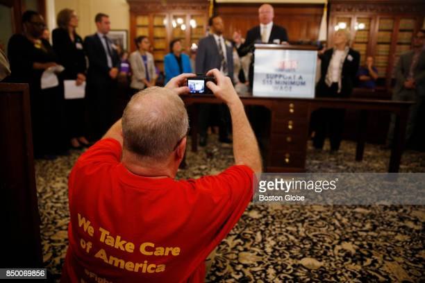 A man takes a picture of Steve Tolman President MA AFLCIO as he speaks during a press conference held to support slowly increasing the state's...