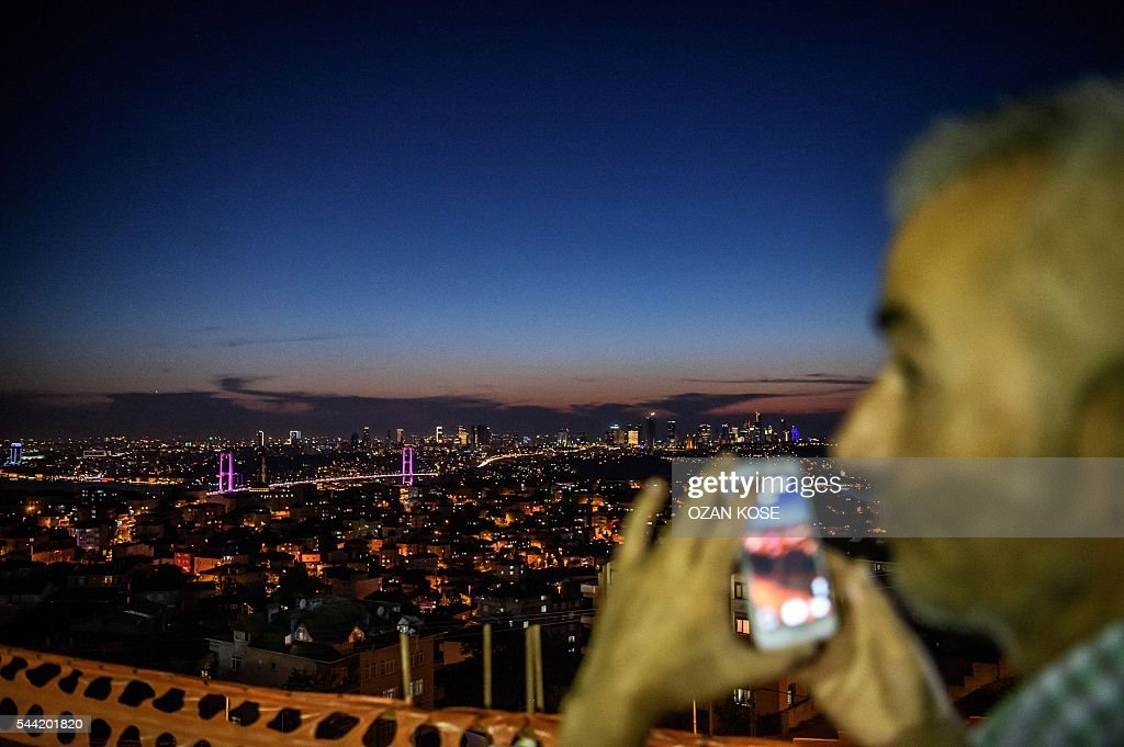 A man takes a picture of the Bosphorus Bridge and the European side of Istanbul on July 1, 2016. Turkey's already limping tourism industry is suffering a fresh grievous blow after the latest in a series of attacks targeted at tourists claimed dozens of lives, analysts said on June 29, 2016. / AFP / OZAN