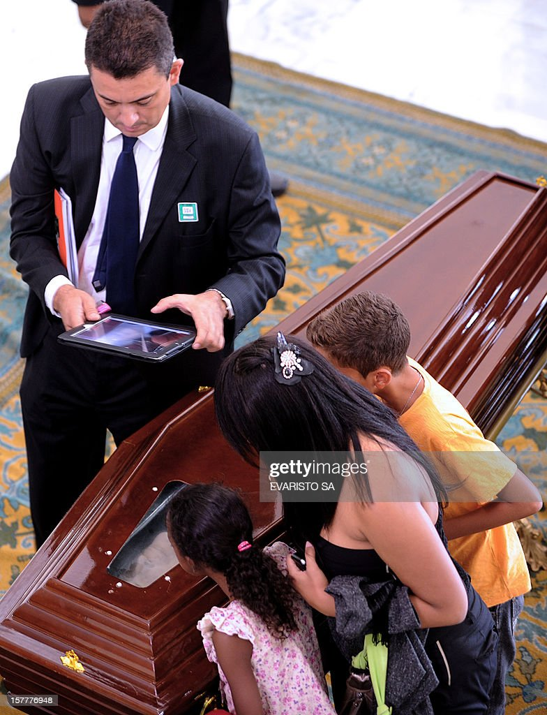 A man takes a picture of the coffin of Brazilian architect Oscar Niemeyer during his funeral at Planalto Palace, in Brasilia, on December 6, 2012. Niemeyer, the Brazilian icon who revolutionized modern architecture and designed much of the country's futuristic capital Brasilia, died in Rio de Janeiro Wednesday at 104. The body will return to Rio de Janeiro for another funeral wake followed by the burial, according to Rio de Janeiro's Mayor Eduardo Paes. AFP PHOTO/Evaristo SA