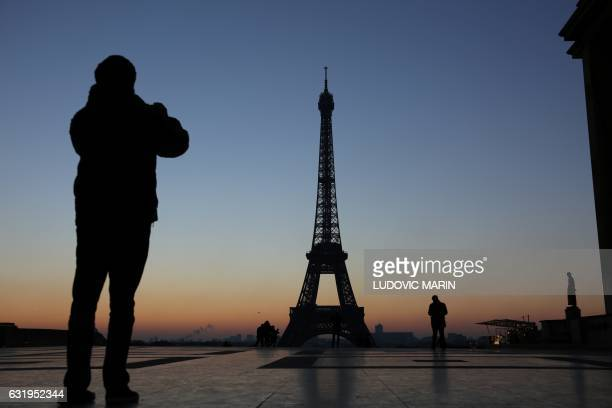 A man takes a picture of the Eiffel tower at sunrise on January 18 2017 on the Place du Trocadero in Paris / AFP PHOTO / LUDOVIC MARIN