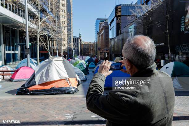 A man takes a picture of the homeless camp at Martin Place on August 6 2017 in Sydney Australia About 50 homeless residents face eviction after the...