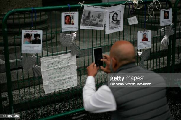 A man takes a picture of the messages left by families of missing persons during a protest to demand the authorities the resolution of the forced...