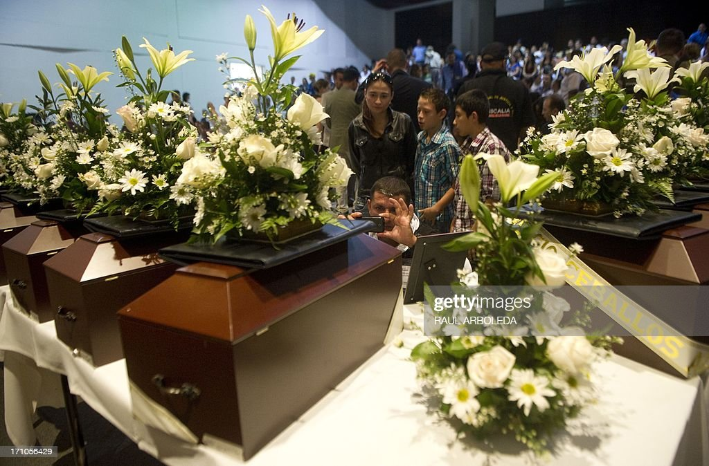 A man takes a picture of the urn with the remains of his relative who was disappeared during the Colombian civil war until recently, on June 21, 2013 in Medellin, Antioquia department, Colombia. In a ceremony, relatives of 36 victims received the remains of their loved ones, which were recently found in common graves due to information given by demobilized combatants of both, leftist guerrillas and right-wing paramilitary groups, in the framework of the country's peace process. AFP PHOTO/Raul ARBOLEDA