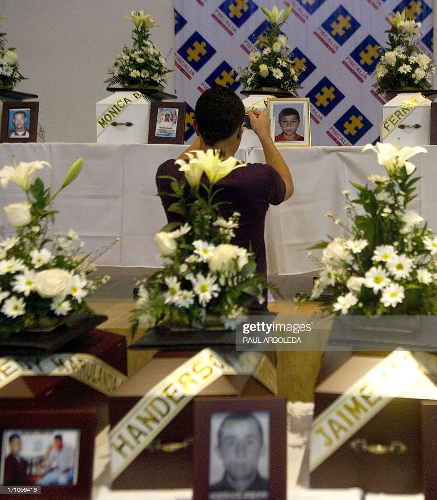 A man takes a picture of the urn with the remains of their relative who was disappeared during the Colombian civil war until recently, on June 21, 2013 in Medellin, Antioquia department, Colombia. In a ceremony, relatives of 36 victims received the remains of their loved ones, which were recently found in common graves due to information given by demobilized combatants of both, leftist guerrillas and right-wing paramilitary groups, in the framework of the country's peace process. AFP PHOTO/Raul ARBOLEDA
