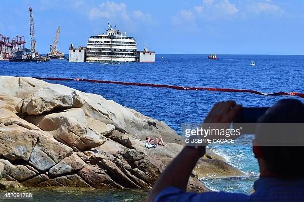 A man takes a picture of the wrecked Costa Concordia cruise ship on July 13 2014 at the Giglio Island Italian authorities gave today their final...