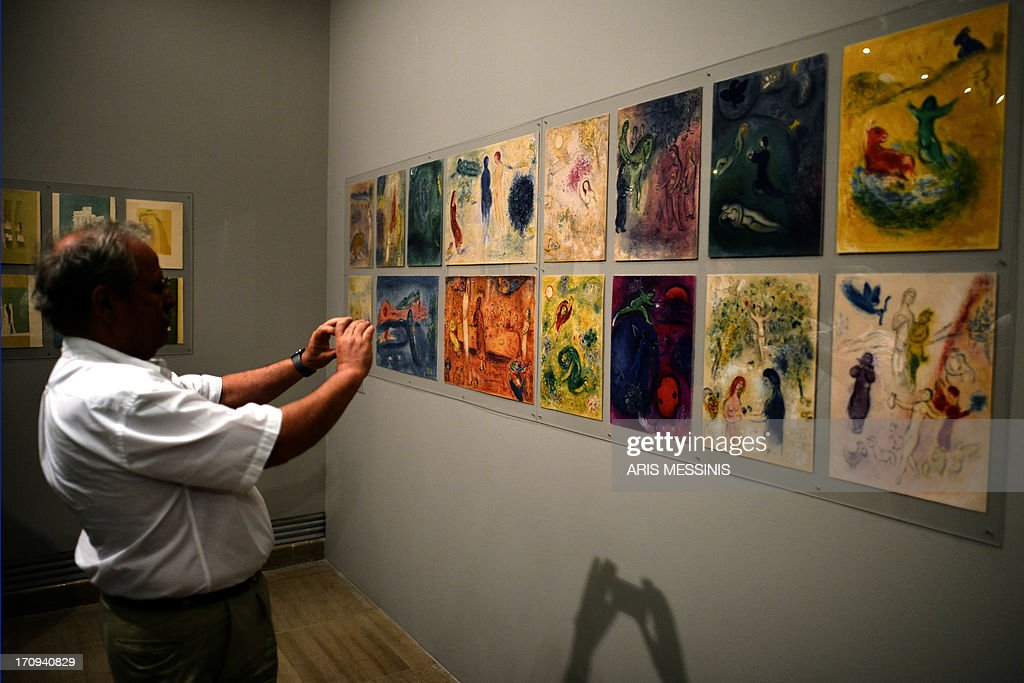 CAPTION -- A man takes a picture of works by Russian artist Marc Chagall at an exhibition of pieces from the Teriade collection at the Museum of Byzantine Art in Athens on June 19, 2013. Pierre Reverdy's 'Song of the Dead' illustrated by Pablo Picasso and Henri Matisse's 'Jazz' are only some of the restored treasures of art editor Teriade, that are currently on display in Athens. The so-called 'Great Books' are housed in the museum that Teriade founded in his native island of Lesvos, in eastern Greece, a building plagued by chronic and severe problems of humidity and high temperatures. Damaged by humidity and bright sunshine, the works were rescued by experts from Athens' Museum of Byzantine Art, who restored them with the help of European funds, urgently granted to the indebted, crisis-hit country.