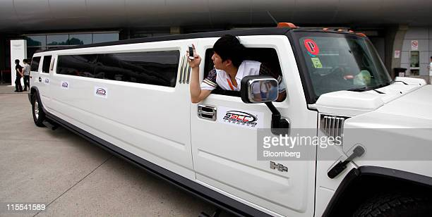 A man takes a picture while leaning out of a Hummer stretch limousine during the Shanghai International Circuit Club Challenge in Shanghai China on...