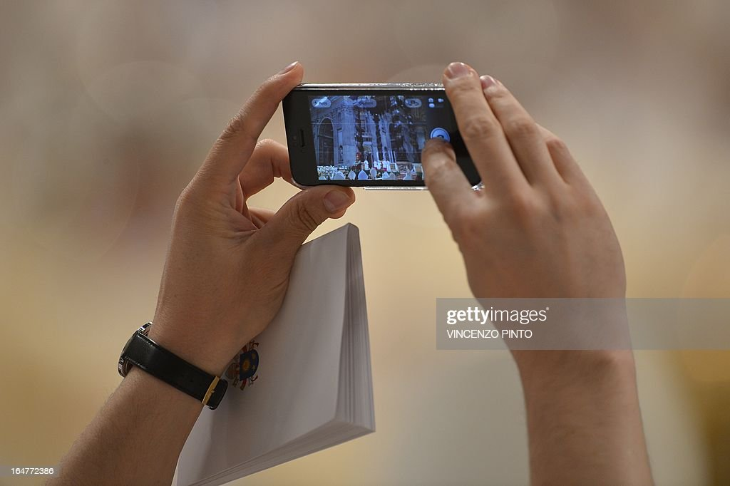 A man takes a picture with an iphone during the Chrism mass on holy Thursday on March 28, 2013 at the St Peter basilica at the Vatican.