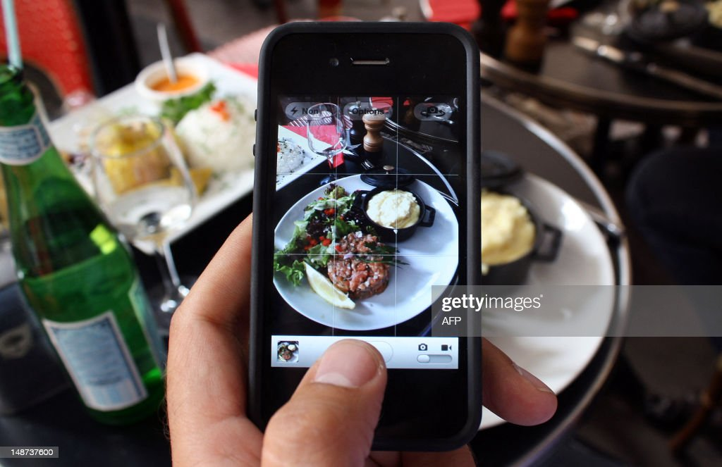 A man takes a picture with his mobile of foods in his plate as he is having lunch on July 19, 2012 in Paris.