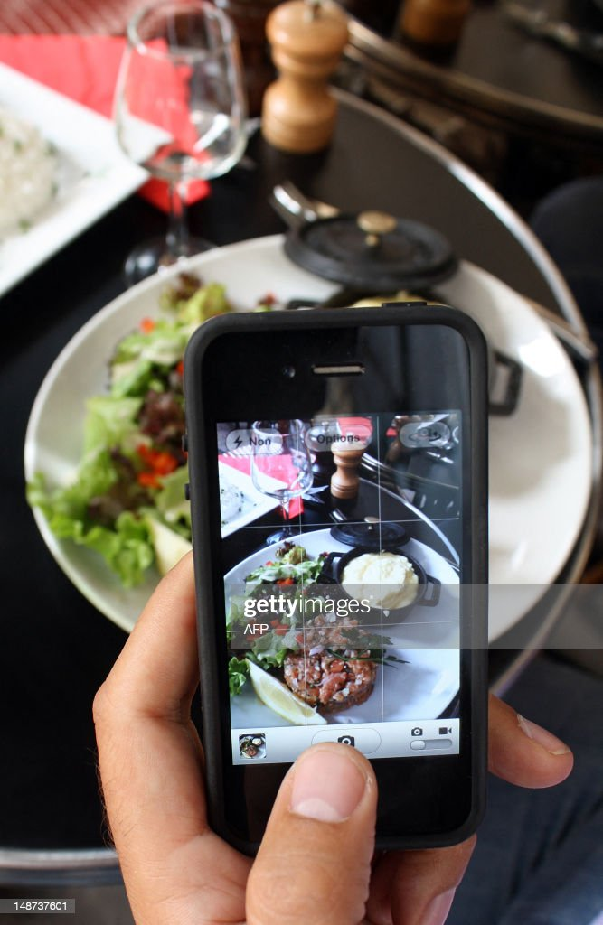 A man takes a picture with his mobile of foods in his plate as he is having lunch on July 19, 2012 in Paris. AFP PHOTO / ANA AREVALO