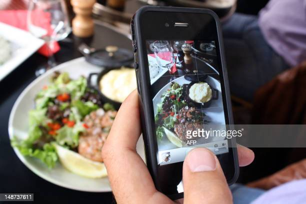 A man takes a picture with his mobile of foods in his plate as he is having lunch on July 19 2012 in Paris AFP PHOTO / ANA AREVALO