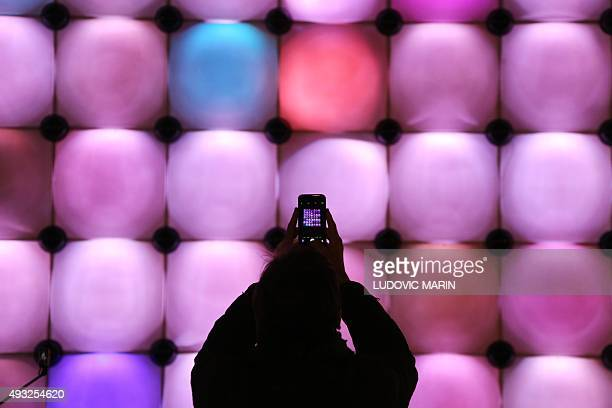 A man takes a picture with his mobile phone in one the 'Sentations Futures' pavilions of French building materials giant SaintGobain temporarily set...