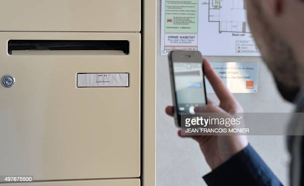 A man takes a picture with his mobile phone on November 18 2015 of the mail box of Fabien Clain a French man identified as the voice in an audio...
