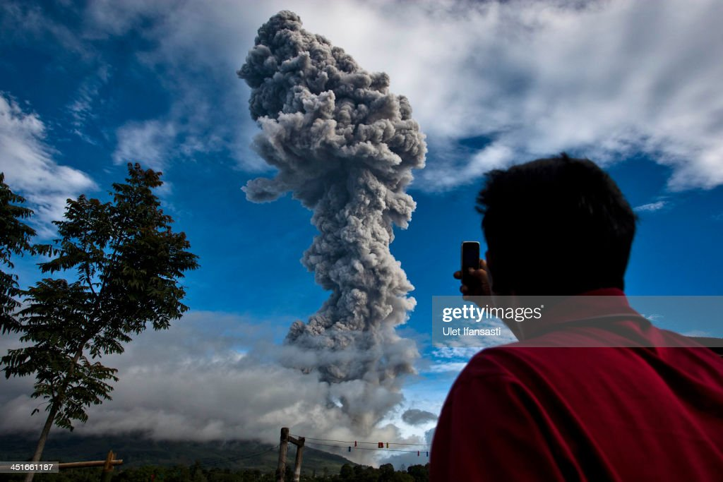 A man takes a picture with his phone as Mount Sinabung spews pyroclastic smoke seen from Tigapancur village on November 24, 2013 in Karo district, North Sumatra, Indonesia. Mount Sinabung, which has been intermittently erupting since September, has erupted eight times in just a few hours overnight. Officials have reported of rocks raining down over a large area, forcing thousands to flee their homes. The Indonesian government has called for people living within five kilometres (3.1 miles) of the volcano, on the northern tip of Sumatra Island, to evacuate their homes as the volcanology agency raised the alert level for the volcano to the highest point on a four-stage scale.