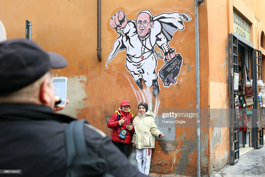 A man takes a picture with his smartphone of his sons posing underneath a graffiti featuring a 'superhero' version of Pope Francis appears in Borgo Pio, next to St. Peter's Square on January 29, 2014 in Rome, Italy. The image started circulating from the twitter account of the Vatican and has rapidly spread around the world.