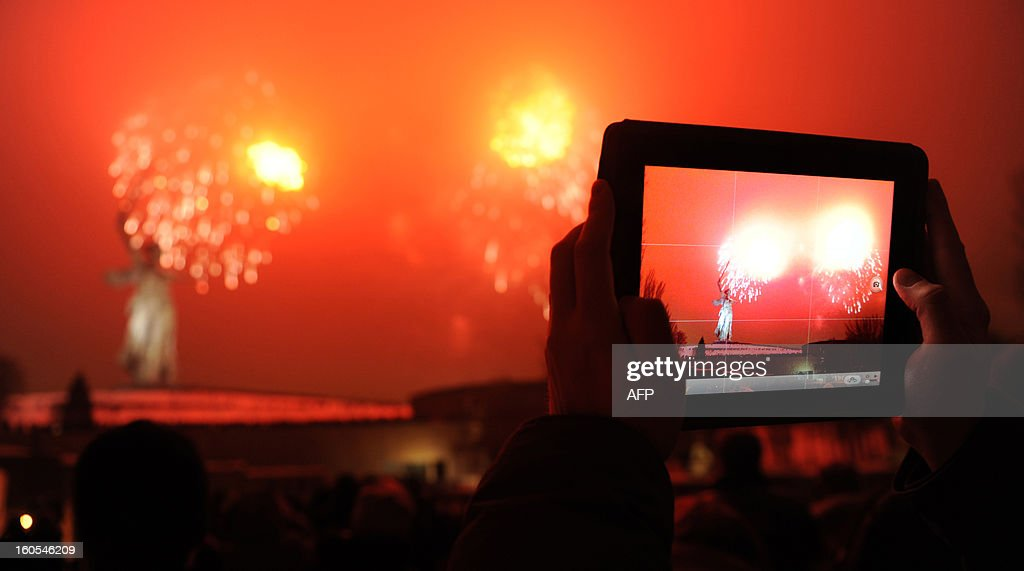 A man takes a picture with his tabled as the fireworks explode over the giant Mother Motherland statue, at the Stalingrad Battle memorial, in the Russian city of Volgograd, late on February 2, 2013. Russia marked today the 70th anniversary of a brutal battle in which the Red Army defeated Nazi forces and changed the course of World War II.