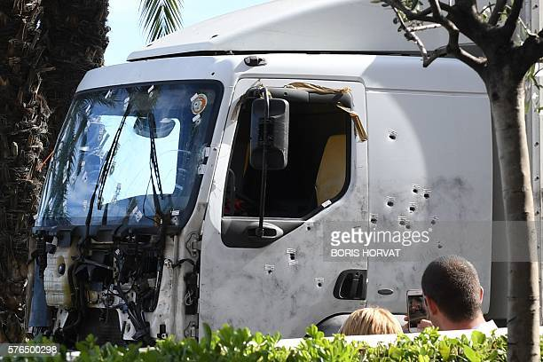 A man takes a pictures as the truck riddled with bullets that was driven by a man through a crowd celebrating Bastille Day is towed away by a...