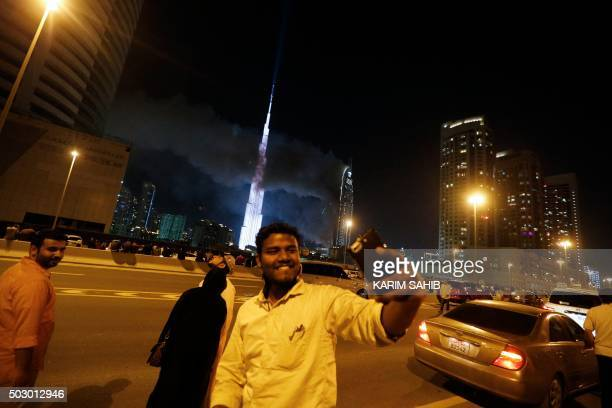 A man takes a selfie as flames rip through the Address Downtown hotel after it was hit by a massive fire near the world's tallest tower Burj Khalifa...