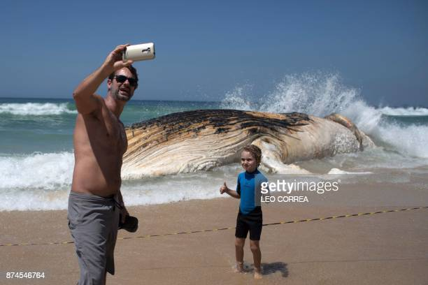 TOPSHOT A man takes a selfie in front of a 12 meters whale that was found dead at Ipanema beach in Rio de Janeiro Brazil on November 15 2017 / AFP...