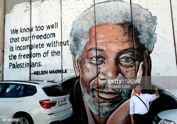 A man takes a selfie in front of a new piece of graffiti depicting US actor Morgan Freeman who played the role of former African president Nelson...