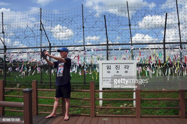 A man takes a selfie in front of a sign board showing the distance to Gaeseong and Seoul at Imjingak peace park near the Demilitarized Zone dividing...