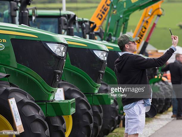 A man takes a 'selfie' in front of tractors displayed for sale on the opening day of the Royal Cornwall Show near Wadebridge on June 4 2015 in...