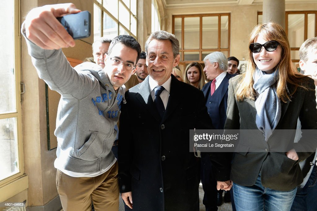 A man takes a selfie of Former French President Nicolas Sarkozy and Carla BruniSarkozy after they have voted on March 23 2014 in Paris France...