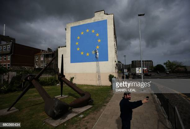 A man takes a 'selfie' photograph with a recently painted mural by British graffiti artist Banksy depicting a workman chipping away at one of the...