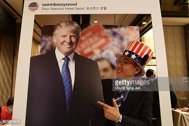 A man takes a selfie with a cutout of Republican presidential candidate Donald Trump during an election watch event on November 9 2016 in Seoul South...