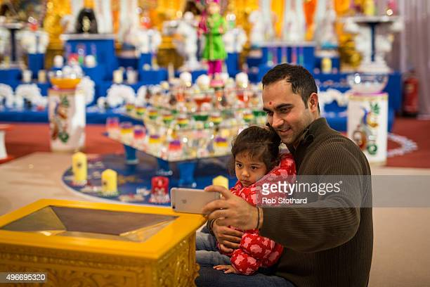A man takes a selfie with his daughter at Shree Swaminarayan Mandir in Kingsbury during Diwali celebrations on November 11 2015 in London England The...
