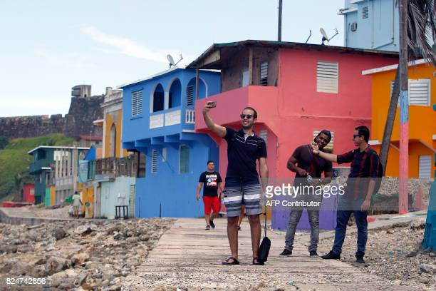 A man takes a selfie with his friends in the neighbourhood of La Perla where the video 'Despacito' was recorded in San Juan on July 22 2017 Something...