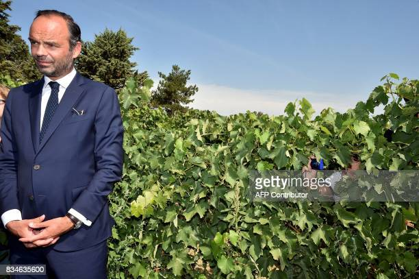 A man takes a snap shot of French Prime Minister Edouard Philippe as he stands in a vineyard during his visit to Domaine du Grand Comté in Roquelaure...