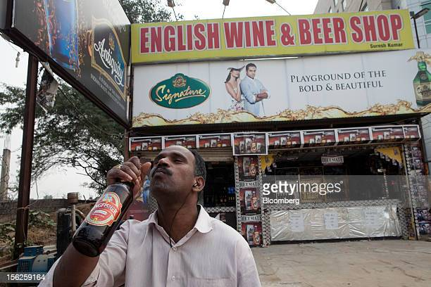 A man takes a swig of Kingfisher beer outside a liquor store displaying an advertisement for United Spirits Ltd Brand whiskeys in New Delhi India on...