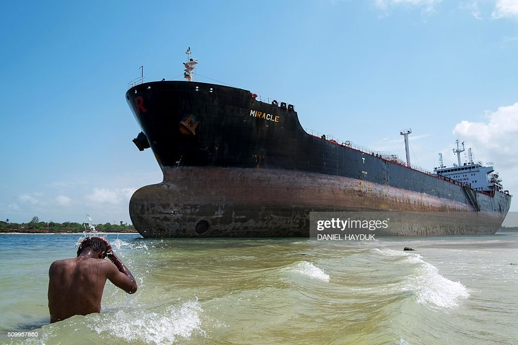 A man takes a swim in the Indian Ocean near the Marshall Islands flagged tanker vessel 'Miracle' after it ran aground at the mouth of the Dar es Salaam's harbour on February 13, 2016. / AFP / DANIEL HAYDUK