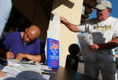 A man takes a voter registration card as Mario Talavera registers to vote at a table sponsored by the League of Women Voters of Diablo Valley October...