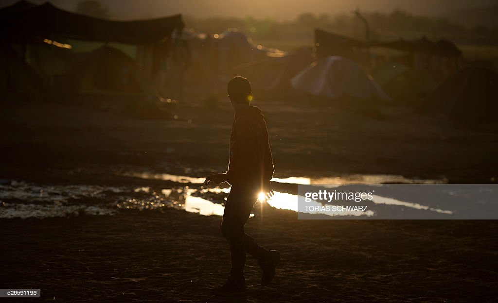 A man takes a walk across a field at a makeshift camp for migrants and refugees near the village of Idomeni not far from the Greek-Macedonian border on April 30, 2016. Some 54,000 people, many of them fleeing the war in Syria, have been stranded on Greek territory since the closure of the migrant route through the Balkans in February. / AFP / TOBIAS