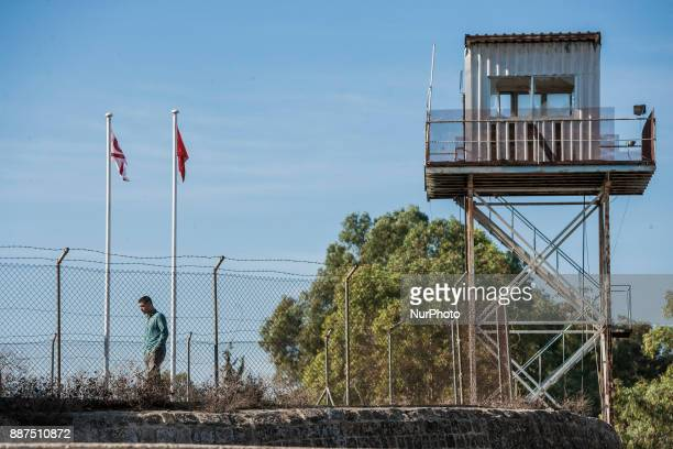 A man takes a walk under a watchtower of the UN in the northern buffer zone that separates turkish and cypriot sides of Nikosia city Cyprus on 3...