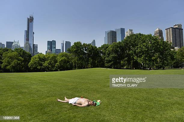 A man takes advantage of the hot weather to sun bathe in the Sheep Meadow in Central Park on May 30 2013 in New York City AFP PHOTO / TIMOTHY CLARY
