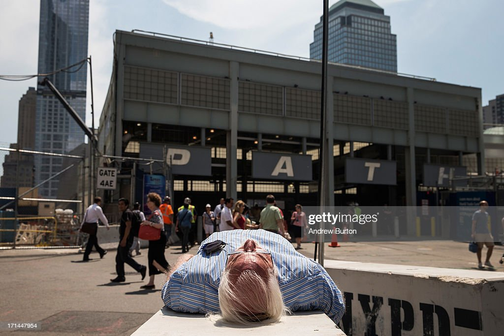 A man takes an afternoon nap on a New York Police Department barricade outside the Ground Zero construction zone on June 24, 2013 in New York City. Construction began on One World Trade Center, the primary building of the new site, on April 27, 2006 and the final piece of the tower was installed on May 10, 2013, making it the tallest building in the Western Hemisphere. Construction is still ongoing on the surrounding complex.